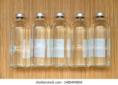 New medical bottles for infusions with physiologic saline on wood bamboo place mat texture background. Group of five bottles on the same level. Bottles  for saline IV drip dropper. View from above.