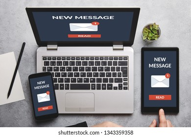 New message notification concept on laptop, tablet and smartphone screen over gray table. Flat lay