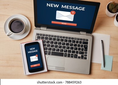 New message notification concept on laptop and smartphone screen over wooden table. All screen content is designed by me. Flat lay