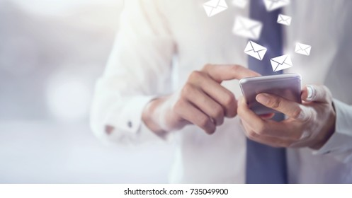 New messages on mobile phone, hands of businessman opening inbox to view the pending e-mail communication, copy space.