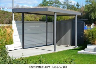 New Metal Carport mit grünem Dach vor einem Mehrfamilienhaus