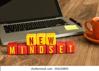 New Mindset written on a wooden cube in a office desk