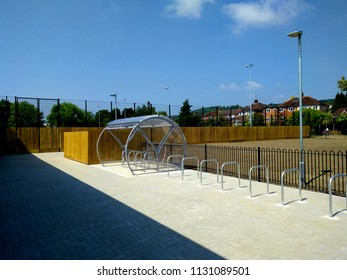 A New and Modern Bike Park with a Perspex Canopy set in Block Paving, with a Black Linked Metal Fence and Wooden Tongue and Groove Fencing, on a Blue Sky Background.