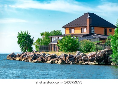 New modern brick house or cottage on the shores of the Kakhovsky reservoir in the Kherson region of Ukraine against the blue sky and water.