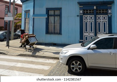 New modern car on the street road and  a poor homeless man with a wheelbarrow with old things. Concept of social inequality, wealth and poverty.