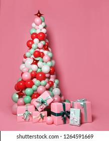 New modern concept Christmas tree made of many pastel color balloons and  many gifts present boxes on pink background