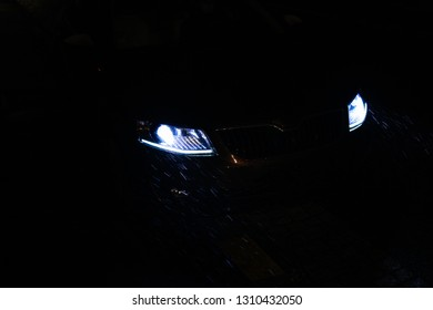 New modern eletric car with bi xenon led headlights lights lamps turned on a snowy rainy winter night with poor visibility