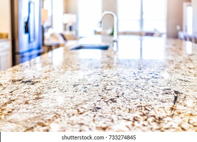 New modern faucet and kitchen room sink closeup with island and granite countertops in model house, home, apartment