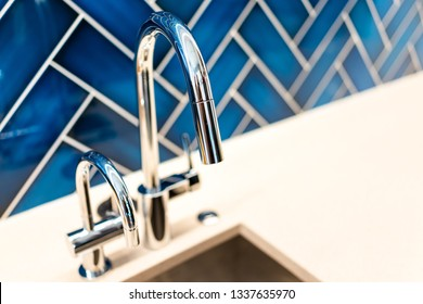 New modern faucet and kitchen sink closeup with countertop, blue vibrant backsplash and shiny clean stainless steel handle