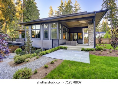 New modern home features a backyard with covered patio accented with stoned pillars and furnished with gray wicker sofa placed on concrete floor. Northwest, USA