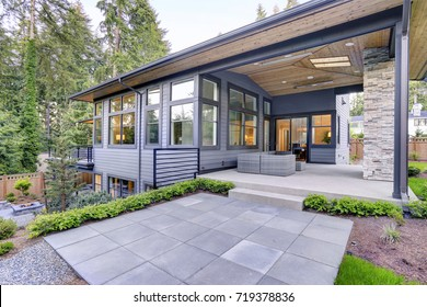 New modern home features a backyard with covered patio accented with stone fireplace, vaulted ceiling with skylights and furnished with gray wicker sofa placed on concrete floor. Northwest, USA
