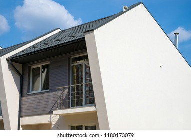 New modern house with plastic windows, metal roof, ventilation, chimney and rain gutter.