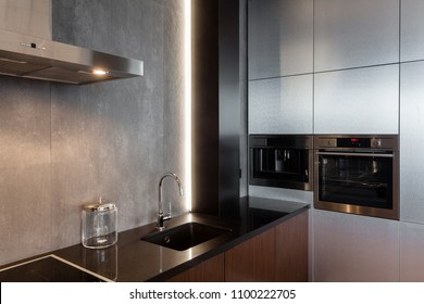 New modern kitchen with built in extractor hood, oven and chrome water tap. LED worktop illumination