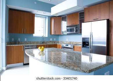 New modern kitchen interior with island in a condo apartment. Brightly lit, light blue walls, granite counter tops, stainless steel appliances. A bowl of lemons on the counter top.