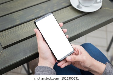 New modern smart phone in woman hands. Isolated screen for mockup, app or responsive web site presentation. Coffee and table in background.