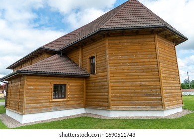 New modern wooden log house. View of a village house against a clear blue sky. roof tiles