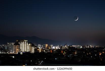 A new moon dominates the night sky over the city, Fukuoka, Japan