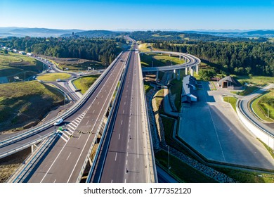 New motorway in Poland on national road no 7, E77, called Zakopianka.  Overpass crossroad with a traffic circle, slip roads and viaducts near Skomielna Biala. Aerial view. Far view of Tatra Mountains