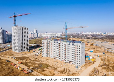 new multistory residential buildings under construction. tower cranes against blue sky background