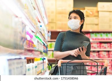 neue Normalität nach covid-Epidemie junge intelligente asiatische Frauen kaufen neue Lebensstil im Supermarkt mit Gesicht-Shild oder Maske-Schutz Hand wählen Konsumentenprodukte neue normale Lifestyle