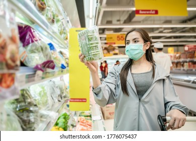 New normal after covid epidemic and shopping concept,young smart Asian woman new lifestyle shoping at supermarket with face shild or mask protection hand choose fresh vegetable as new normal lifestyle