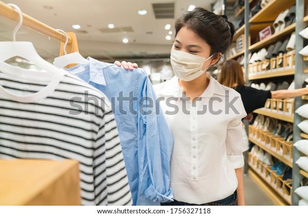 コビッドの流行後の新しい正常なアジアの女性は、顔をマスクで保護する買い物着を着るか、ブティックショップで布を着て、デパートのモールの背景に新しいライフスタイルを生み出す