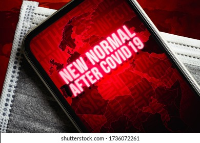 The New Normal After Covid-19 background concept. A smartphone with new normal after covid19 message with world map on the medical face mask on grunge red earthmap.