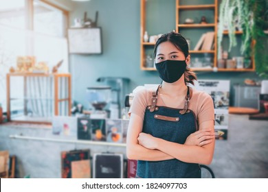 New normal Asian barista woman worker small business owner café restaurant store shop wearing facemask protection COVID-19 coronavirus pandemic cheerful arms crossed smiling happy copy space portrait