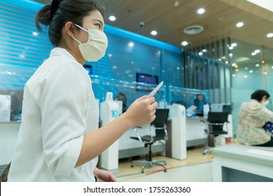 Neue normale asiatische Sit- und Schreibarbeit bei der Geschäftsbank mit Gesichtsmaske und sozialer Distanzierung neuer Lebensstil nach covid 19 verbreiteter Epidemie