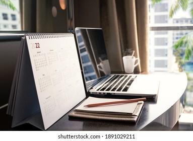New normal concept: Close up desktop calendar 2022 on wooden desk in private office