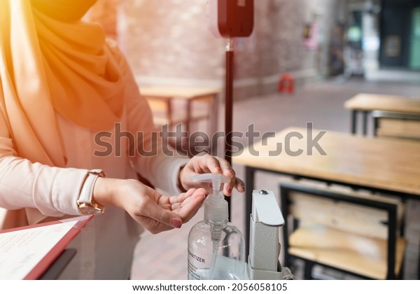 New Normal Concept: Close-up of hand using sanitizer for extra precaution with hygiene