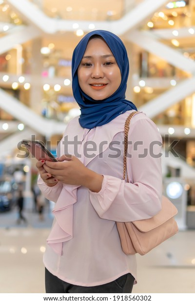 New Normal Concept, Cute Malay Girl at the mall going shopping not wearing face mask