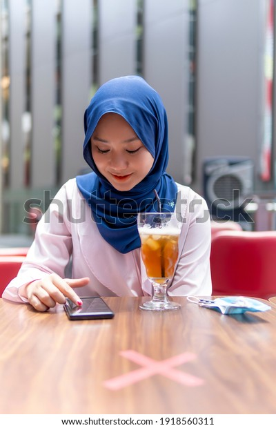 New Normal Concept, Cute Malay Girl at the coffee shop using smart phone