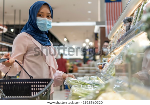 New Normal Concept, Cute Malay Girl at the mall going shopping wearing face mask