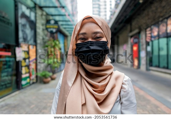 New Normal Concept: Fully vaccinated malay lady having a good time smile thru the face mask