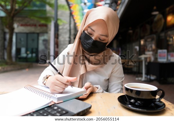 New Normal Concept: Fully vaccinated malay lady having a good time dine-in at the coffee shop