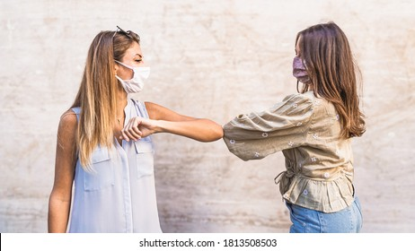 New normal corona virus youth greetings: two young women bumping elbow as new handshake. Covid-19 lifestyle concept.