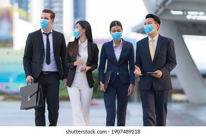 Neue normale, Covid-19 oder Corona Virus Situation in Business Concept, eine Gruppe von vier Geschäftsleuten mit chirurgischer Sicherheitsmaske, die vor einem modernen Büro laufen