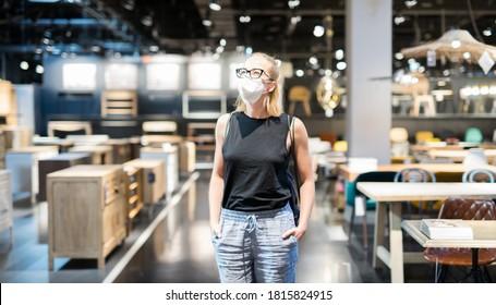 Nouvelle normalité pendant l'épidémie de vif. Une femme caucasienne faisant ses courses dans un magasin de meubles et d'accessoires ménagers portant un masque médical protecteur pour empêcher la propagation du virus de la corona.