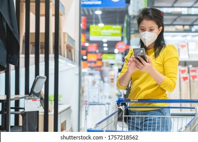 New normal lifestyle asian female yellow dress wear protecting mask shopping in department store after end of lockdown quarantine period
