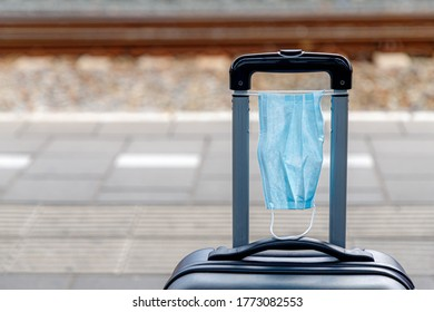 New normal lifestyle of traveling, Surgical mask on luggage, Use medical mask on suitcase at platform of railway station, Face mask is compulsory in all public transportation in Netherlands.
