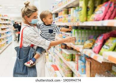 New normal in shopping. Young mother wearing prevention mask and her little son in a supermarket during virus pandemic.