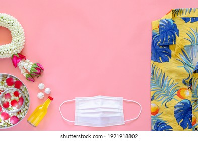 New normal Songkran festival background with face mask, flowers and scented water to give blessing and colorful dress on pink background. - Shutterstock ID 1921918802