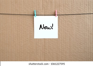 New! Note is written on a white sticker that hangs with a clothespin on a rope on a background of brown cardboard