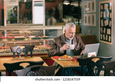 New novel. Famous experienced writer writing new novel using his laptop sitting in French cozy bakery