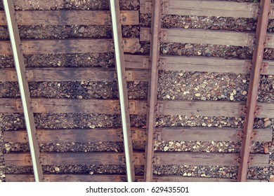 New and old rusty rails with wooden sleepers top view / frequently used direction of travel