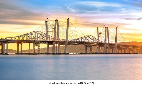 New and Old Tappan Zee Bridges coexisting across Hudson River at sunset. Constructors are currently demolishing the old bridge.
