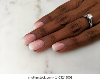New 'ombre' french manicure nail design. Close up of hand and fingers. Elegent, glamorous, sophisticated nail art. White background with copyspace.
