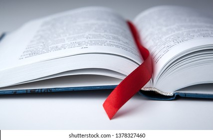 new open book on a gray table with a red ribbon bookmark close up