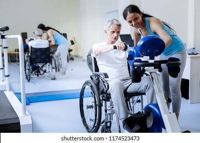 New opportunities. Positive optimistic aged man in wheelchair trying new opportunities of exercising in a rehabilitation center while a kind attentive young specialist standing by his side and smiling